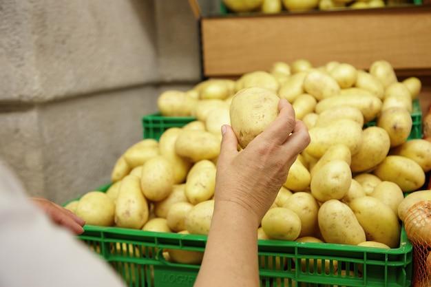 Подрезанный портрет старшей кавказской женщины протягивая руку с большой картошкой в ней, готовый положить ее в свою корзину, делая покупки в супермаркете, ища овощи для приготовления семейного ужина