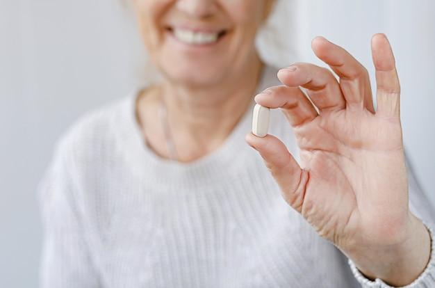 영양 보충제와 물 한 잔을 들고 웃는 노인 여성의 자른 된 초상화. 선택적 초점, 예방 접종 개념