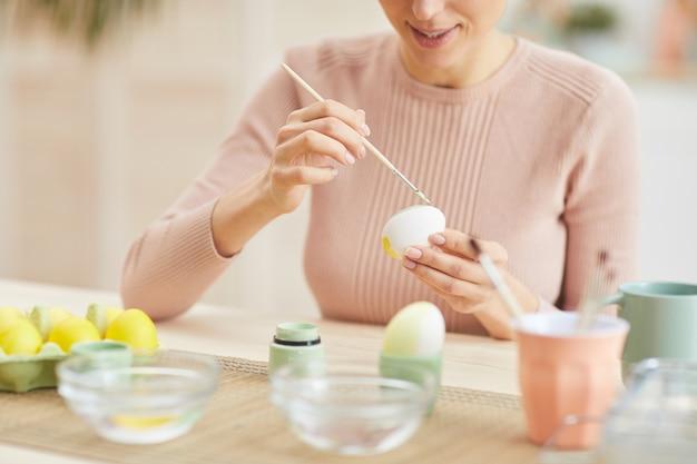 居心地の良いキッチンインテリア、コピースペースのテーブルに座ってイースターエッグを描く笑顔の若い女性のトリミングされた肖像画