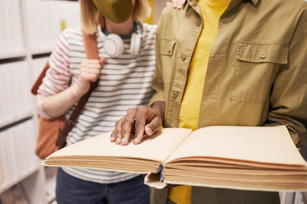 図書館のコピースペースで視覚障害者の友人を助ける学生のトリミングされた肖像画