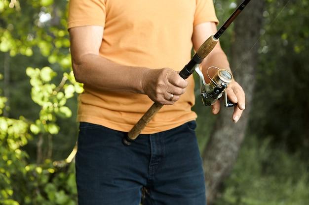 야생의 자연 환경에서 야외에서 낚시하는 동안 오렌지 티셔츠와 낚시 도구를 사용하여 검은 청바지를 입고 인식 할 수없는 노인 어부의 자른 초상화. 어업, 활동 및 취미 취미