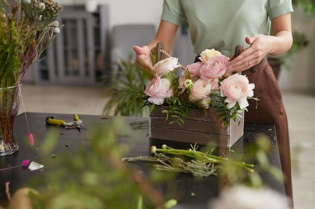 花屋のワークショップ、コピースペースで働いている間ピンクの牡丹と花の構成を配置する認識できない若い女性のトリミングされた肖像画