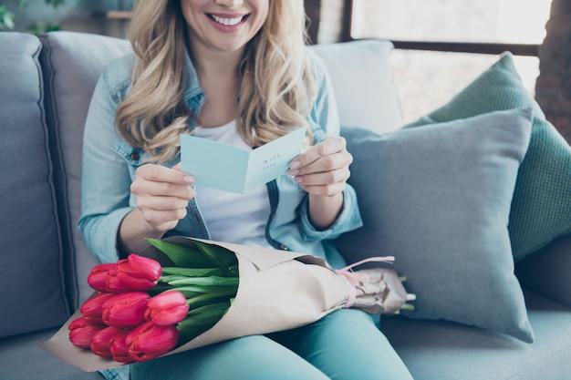 ポストカードを読んでソファに座っている女性のトリミングされた肖像画は花を保持します