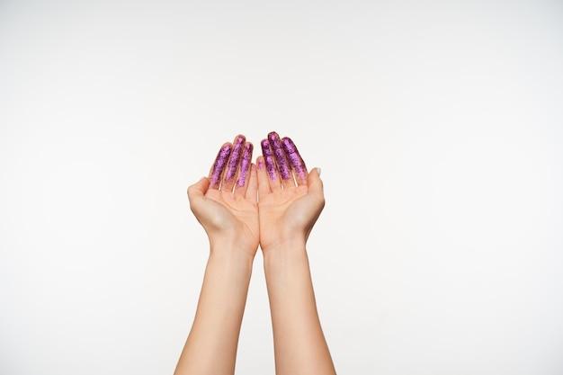 젊은 공정한 피부 여자의 자른 된 초상화는 parkles 손바닥을 제기 하 고 함께 형성, 흰색에 서있는 페인트. 손과 제스처 개념