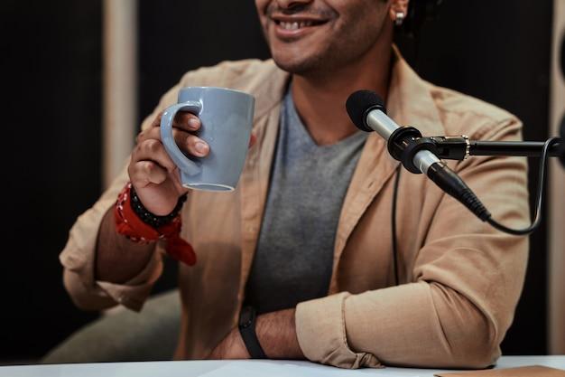 방송하는 동안 커피를 마시며 웃고 있는 헤드폰을 끼고 있는 젊은 남성 라디오 진행자의 자른 초상화