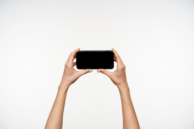Cropped portrait of raised fair-skinned woman's arms keeping mobile phone horizontally while going to watch video on it, standing on white
