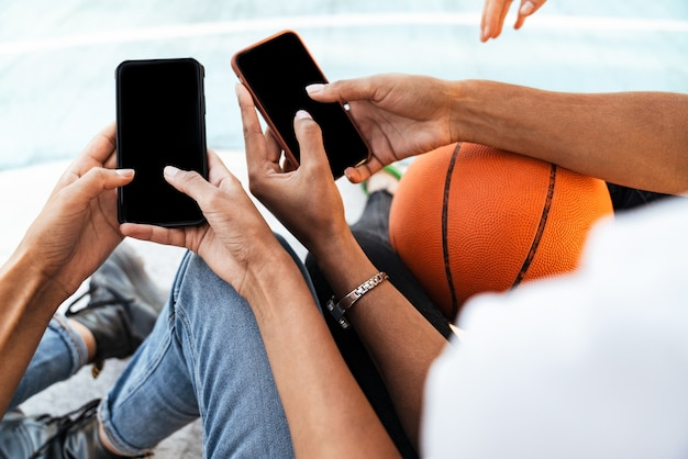 Cropped portrait of two young african american girls in trendy streetwear sitting on playdround with basketball and smartphones
