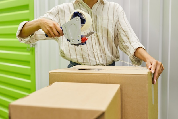 Cropped portrait of unrecognizable young woman packing boxes with tape gun while standing by self storage unit, copy space