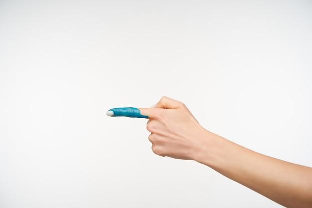 Ritagliata il ritratto della mano della giovane donna con il manicure bianco mantenendo l'indice sollevato mentre indica da parte, isolato su bianco. concetto di corpo umano