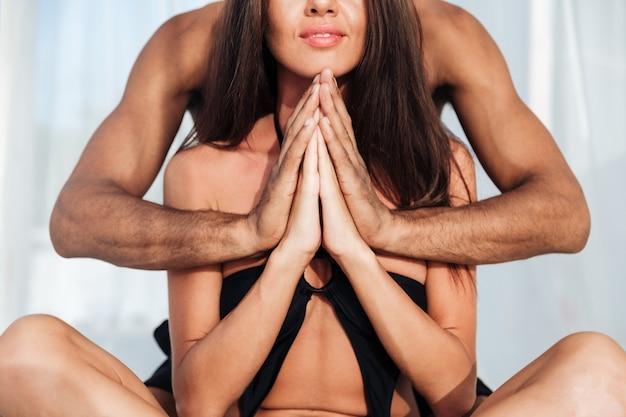 一緒に仲介し、ビーチで蓮華座に座っている美しい多民族のカップルのクロップドポジション