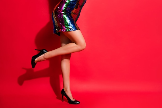 매력적인 소녀 긴 다리의 자른 프로필 사진은 광택이 나는 짧은 드레스 하이힐을 신고 선명한 붉은 색 배경을 격리합니다