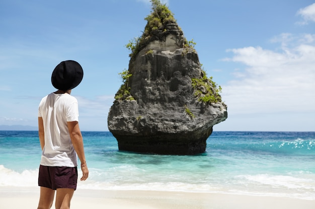 Cropped rear shot of fashionable male model wearing black hat, t-shirt and shorts standing on sand in front of rocky cliff in middle of ocean while posing on beach