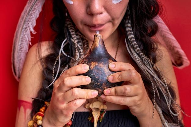 赤い壁に隔離された本物のインドの笛を使用してトリミングされたシャーマンの女性、頭のシャーマニズムに羽を持つ女性。顔の半分の肖像画のクローズアップ