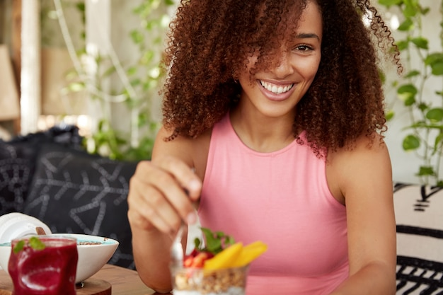 Cropped shot of adorable female model with curly dark hair, dressed in pink casual t shirt, eats dessert, smiles broadly. mixed race young african american woman poses against cafe interior.