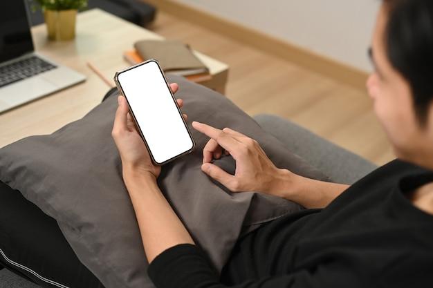 ソファで休んで携帯電話を使用しているクロップドショットアジア人男性。