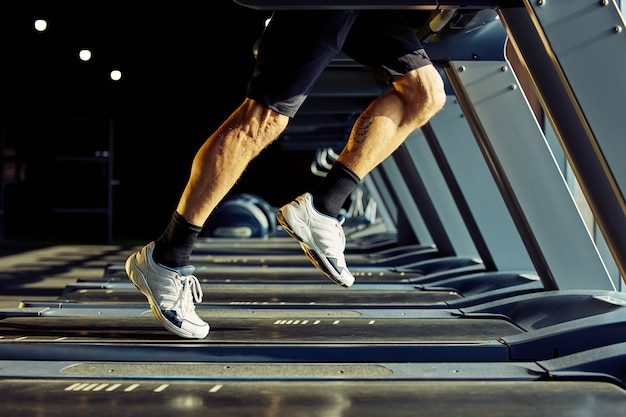 Cropped shot of athletic man in sportswear running on a treadmill in a gym focus on legs