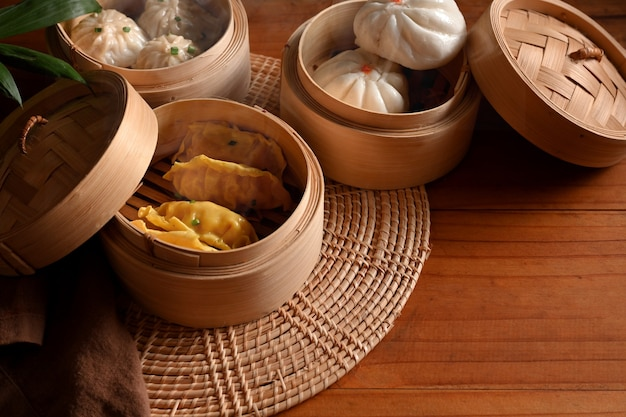 Cropped shot of bamboo steamers with dumplings and pork bun on wooded table in kitchen