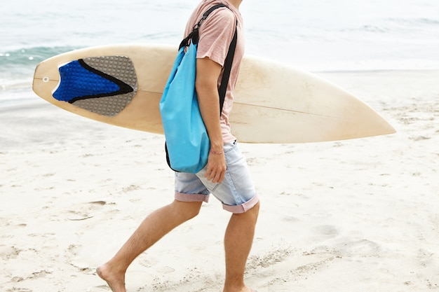Cropped shot of barefooted man with blue bag carrying white surfboard in his hand, walking along sandy coast while returning home after active surf training with other surfers