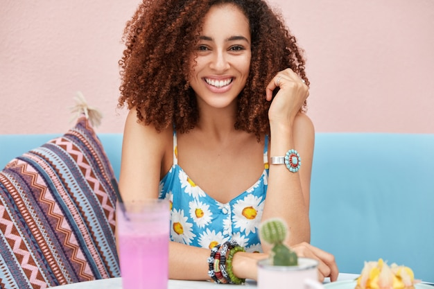 Cropped shot of beautiful african american female with curly hair, broad smile, enjoys leisure time in cafeteria, surrounded with fresh summer drink
