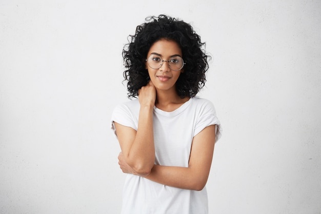 Cropped shot of beautiful friendly cute smiling young african american woman posing with closed posture, slightly smiling, having shy look, wearing spectacles. human emotions and gestures