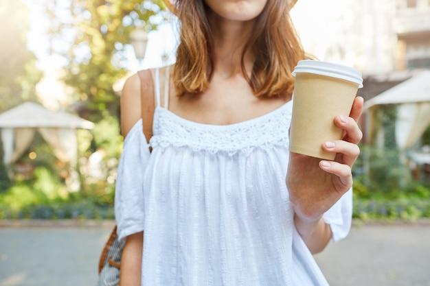 Ritagliata colpo di bella giovane donna indossa abito estivo bianco che tiene tazza di caffè da asporto e passeggiate all'aperto nella città vecchia