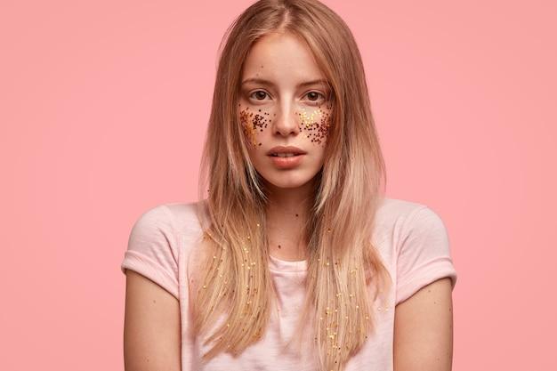 Ritagliata colpo di bella giovane donna con i capelli biondi, la pelle sana, ha scintillii sulle guance, viso decorato, si prepara per un evento festivo, vestito con una maglietta casual, si erge contro il muro rosa