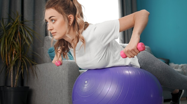Cropped shot of beauty with dumbbells in arms bent at elbows lying on fitness ball training at home