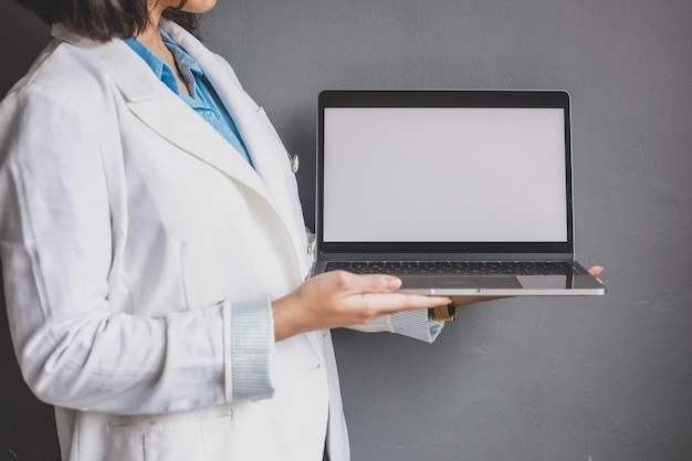 Cropped shot of business woman holding blank white screen laptop on grey background