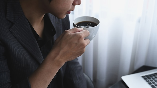 Обрезанный снимок бизнесмен пить кофе и читать новости на портативном компьютере.