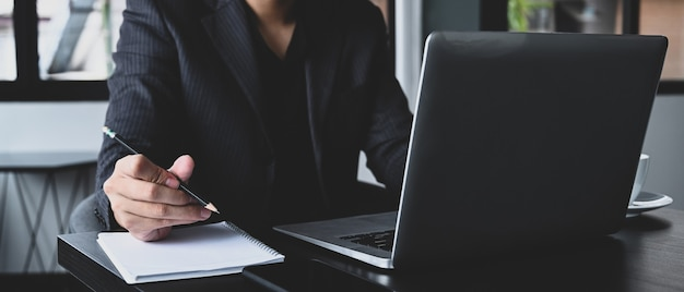 Обрезанный снимок бизнесмена в костюме, работающего с ноутбуком в современном офисе.