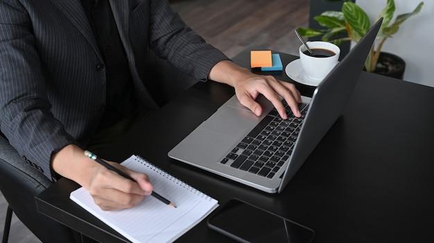 Обрезанный снимок бизнесмена, делая ноутбук понятие и используя ноутбук на офисном столе.