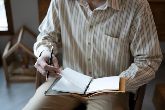 Обрезанный снимок бизнесмена, сидящего на удобном рабочем месте и читающего книгу.