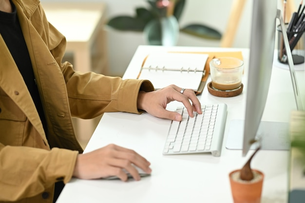 Обрезанный снимок бизнесмена, сидящего на современном рабочем месте и работающего с компьютером.