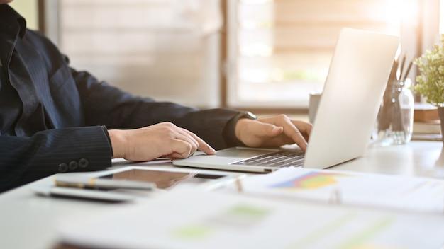 Cropped shot businessman using laptop computer.