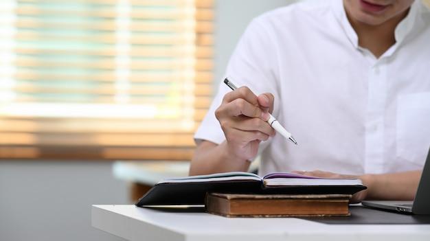 Обрезанный снимок бизнесмен писать ноутбук с ручкой на столе в домашнем офисе.