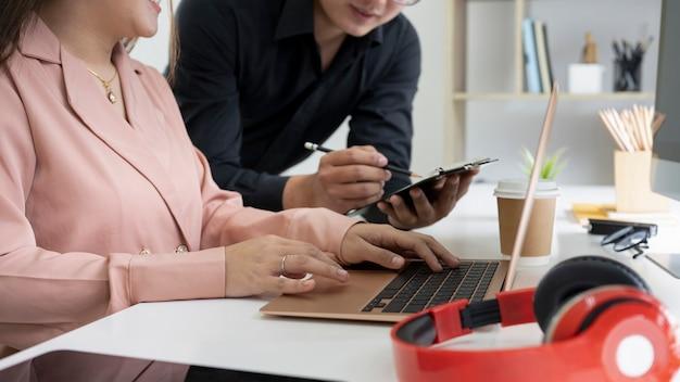 디지털 태블릿을 사용하고 사무실에서 정보를 공유하는 비즈니스맨을 잘랐습니다.