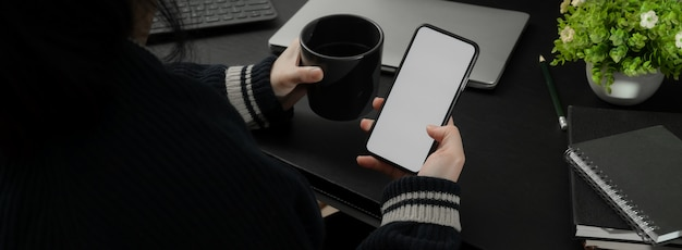 Cropped shot of businesswoman relaxing with hot coffee and  smartphone