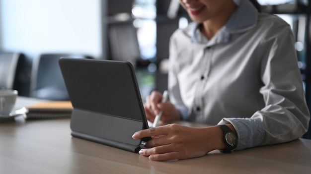 Cropped shot of businesswoman searching information on computer tablet at office desk.