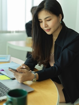 Cropped shot of businesswoman using smartphone while sitting at workplace