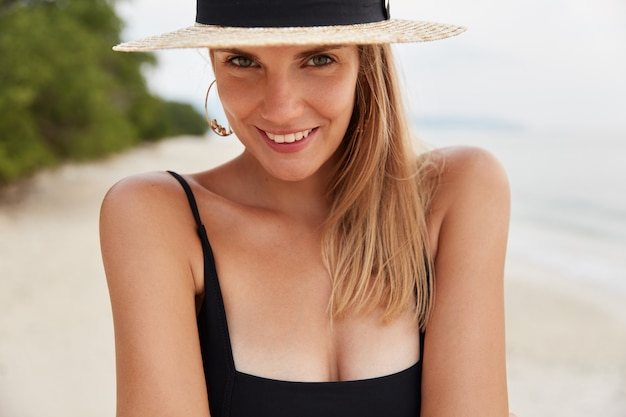 Cropped shot of cheerful female model in straw hat and black bikini, strolls across beach near calm ocean, has positive expression. beautiful young woman wears bathing suit, has perfect body shape