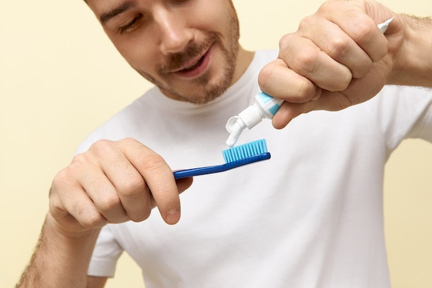Cropped shot of cheerful healthy young caucasian man in white t-shirt squeezing paste on toothbrush, brushing teeth after waking early in the morning.