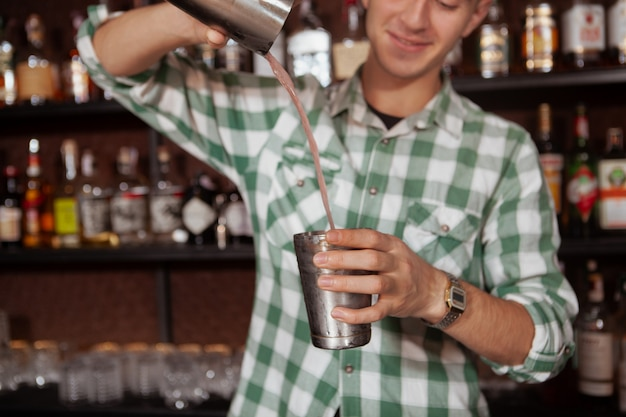 Cropped shot of cheerful professional bartender preparing cocktail for a customer, using steel shaker tin