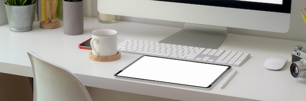 Cropped shot of comfortable office desk with blank screen tablet and office supplies