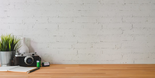 Cropped shot of comfortable workplace with camera and office supplies on wooden table and brick wall