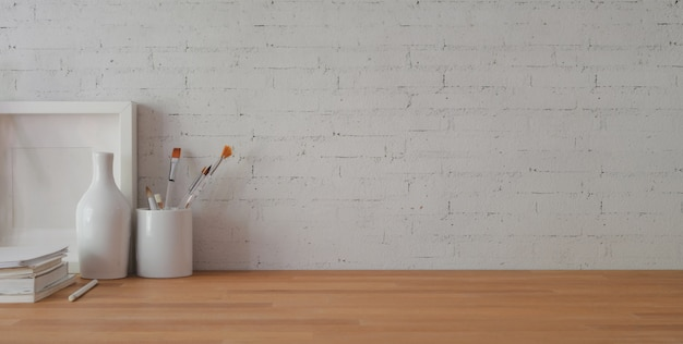 Cropped shot of comfortable workplace with office supplies and copy space on wooden table and brick wall