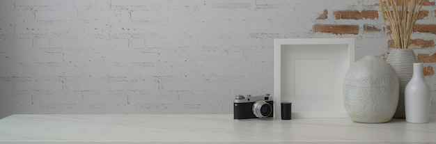 Cropped shot of contemporary workspace with frame, ceramic vases, camera and copy space