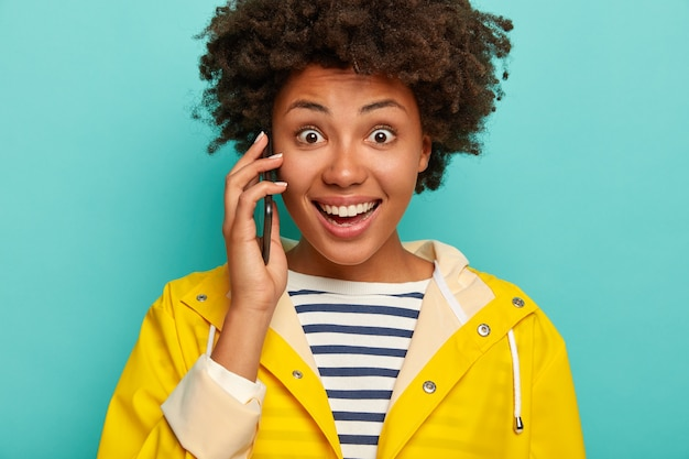 Ritagliata colpo di giovane donna sorpresa dalla pelle scura utilizza un cellulare vestito con maglione a righe e impermeabile giallo