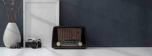 Cropped shot of dark stylish workplace with mock up frame, vintage radio and decorations