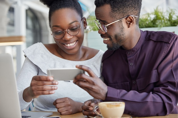 Cropped shot of deighted happy african couple holds smart phone horizontally, watch interesting video, have coffee break, smile joyfully, wears round spectacles.