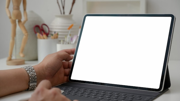 Cropped shot of designer typing on digital tablet with painting tools on white table